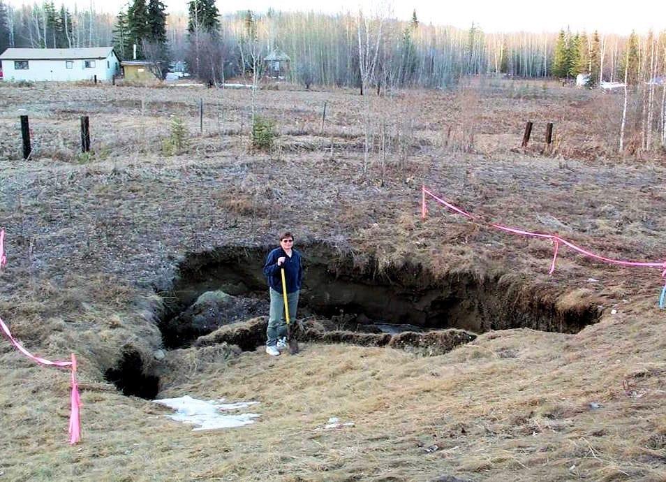 Der Permafrost-Forscher Vladimir Romanovsky von der Universität Alaska Fairbanks posiert vor einem Bereich, wo der Boden durch den Verlust des Permafrostes eingebrochen ist. Gemäss dem Forscher müssen sich die Bewohner arktischer Regionen häufiger auf solche Ereignisse vorbereiten. Bild: UAF